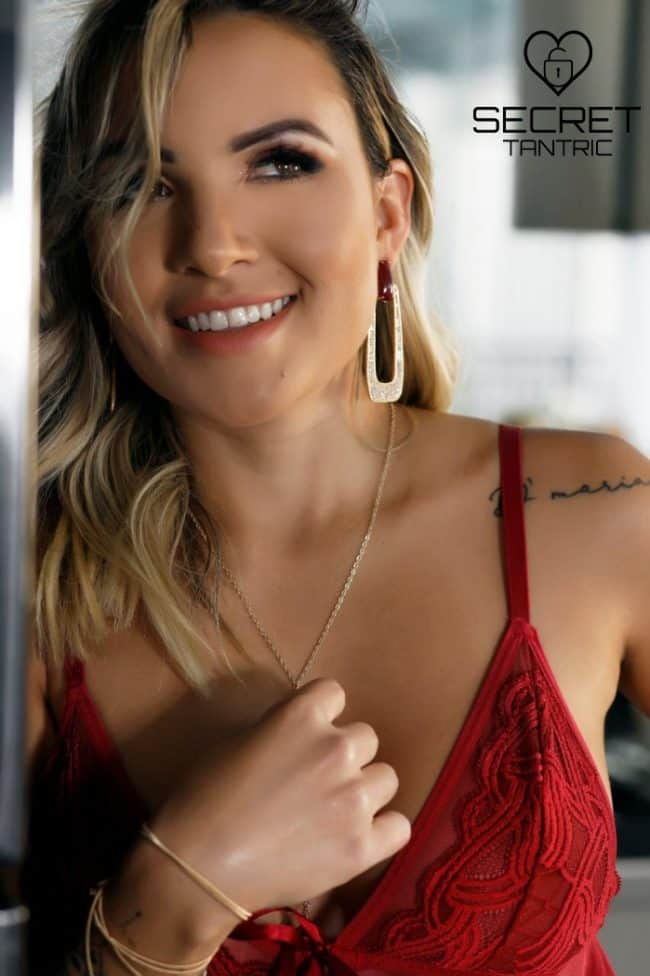 Deborah - Smiling tantric and erotic masseuse playing with necklace| Secret Tantric London